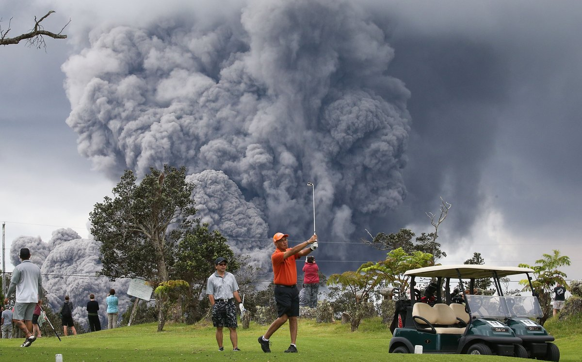 Hawaiian Golfers with volcano ash and smoke in the background;