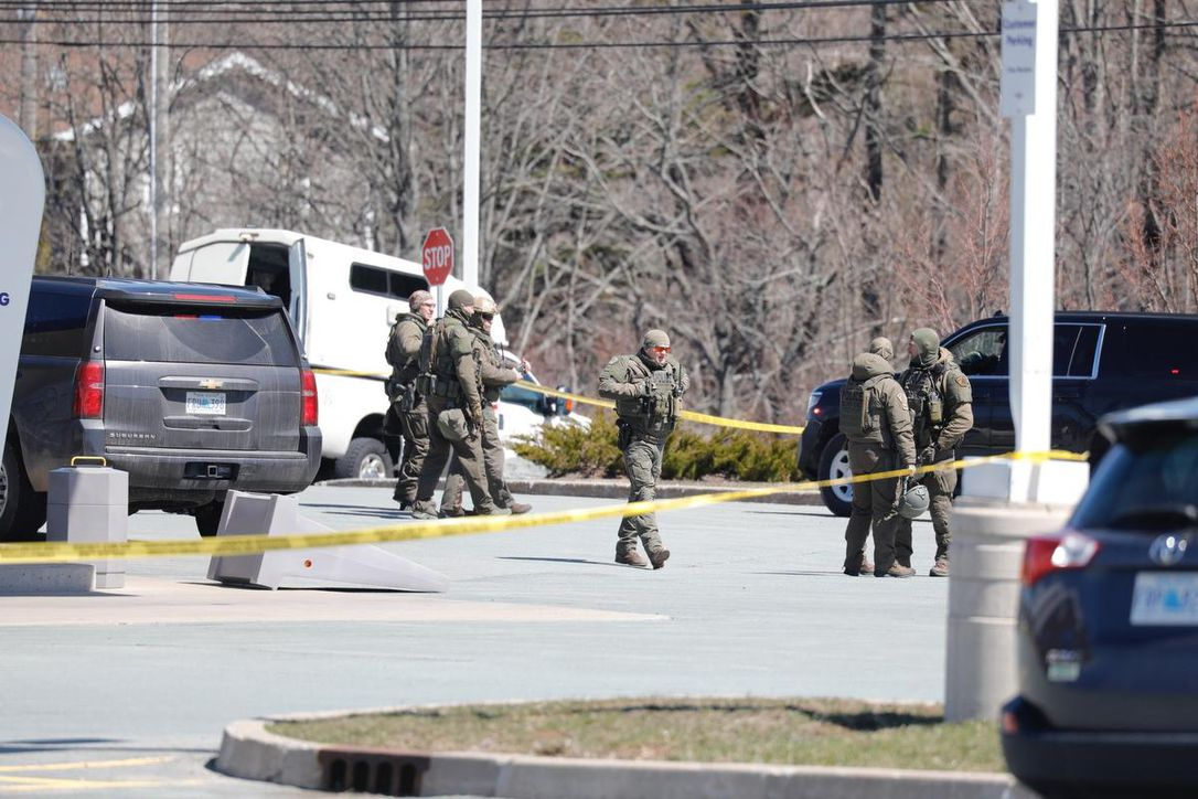 RCMP Officers standing outside a scene of the shooting caused by 51-year-old Gabriel Wortman;