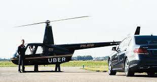 A man standing next to a helicopter, with Uber's name written on it, waiting for a customers to get out of his car;